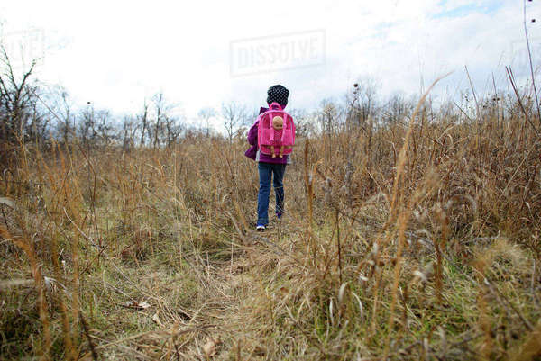 Rear view of girl with backpack walking on dry grassy field Royalty-free stock photo