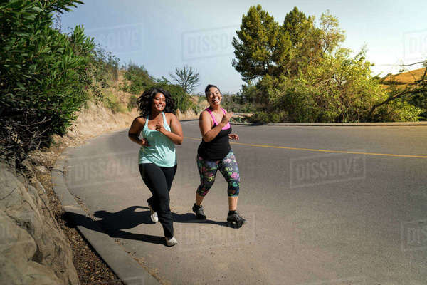 Happy female friends jogging on road during sunny day Royalty-free stock photo