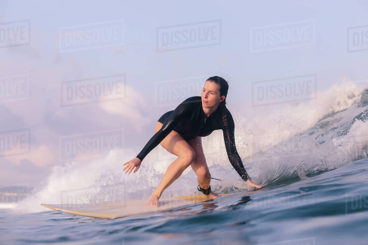 Low Angle View Of Woman Surfing In Sea Against Sky Stock Photo