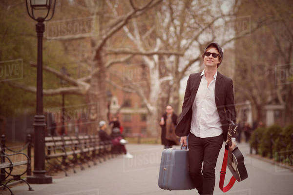 Portrait of man walking along park alley carrying with acoustic guitar and suitcase Royalty-free stock photo