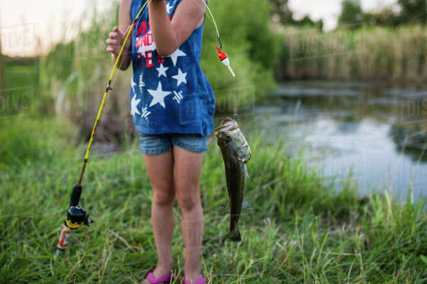 Midsection of girl holding caught fish in fishing rod while standing by lake Royalty-free stock photo