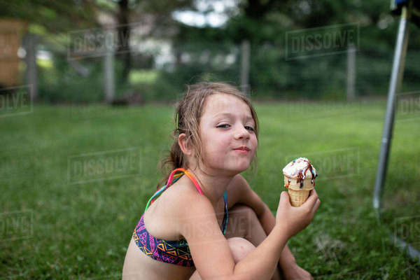 Portrait of girl holding ice cream cone while sitting in yard Royalty-free stock photo