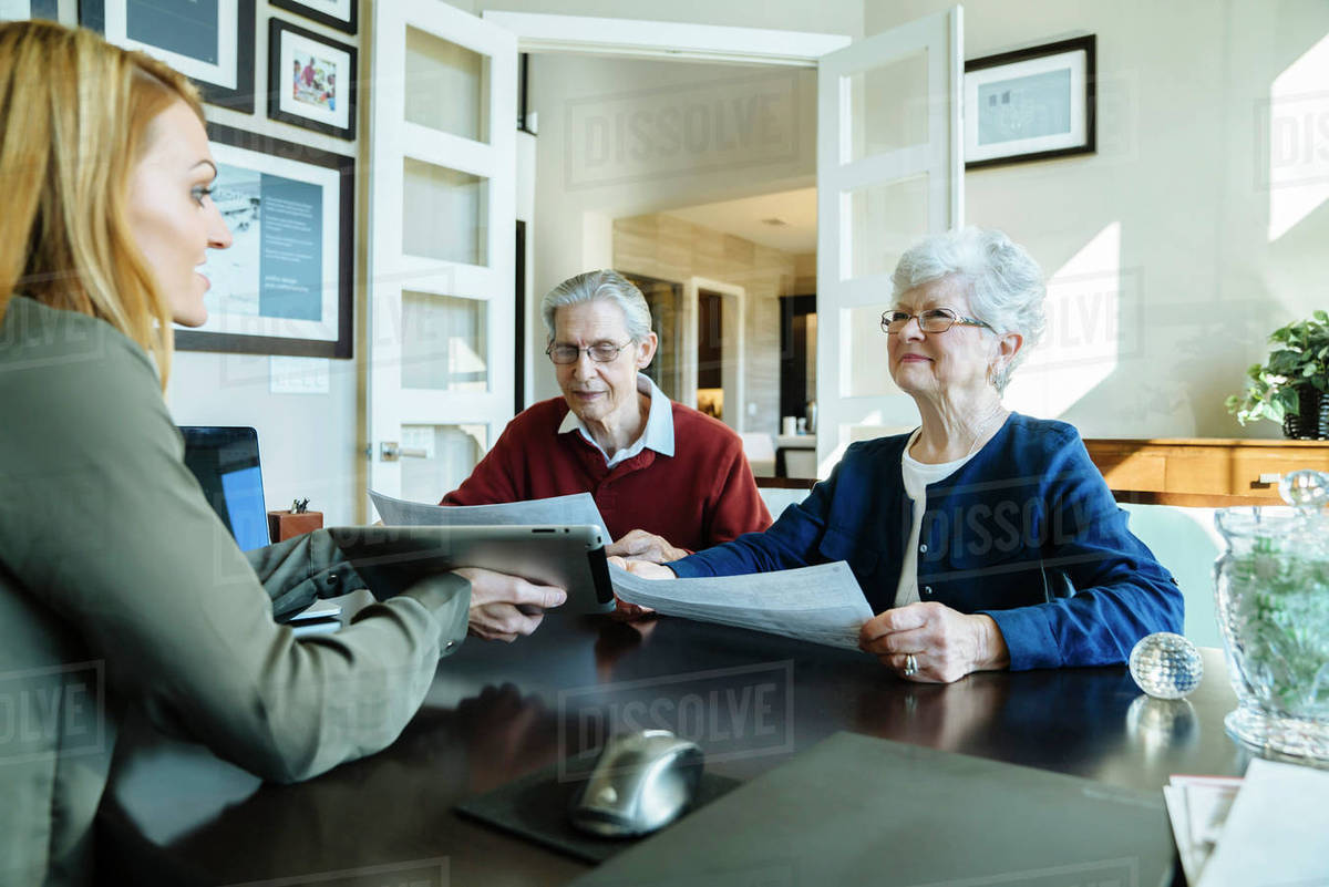 Senior Couple Holding Documents While Discussing With Financial Advisor In  Office