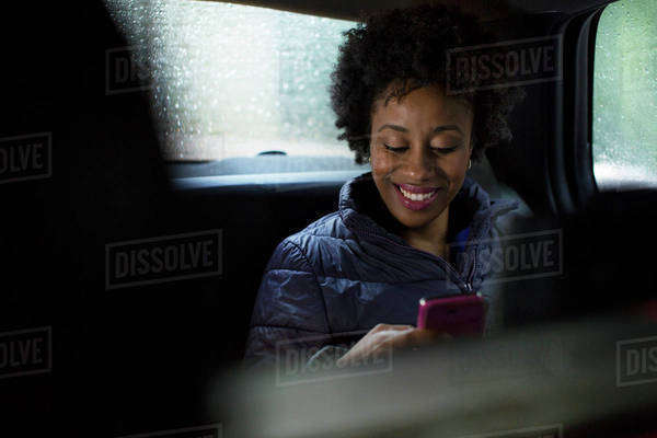 Smiling woman in backseat of car using smart phone Royalty-free stock photo