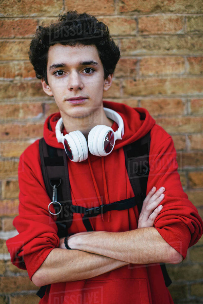 Portrait Of Confident Teenage Boy With Backpack And Arms Crossed Standing Against Brick Wall Stock Photo