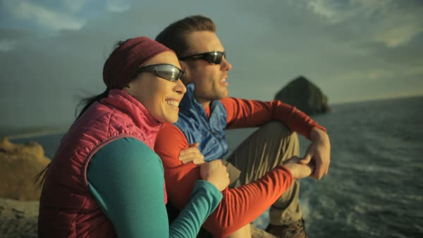 Handheld shot of happy hiking couple enjoying wind while sitting on rock by sea Royalty-free stock video