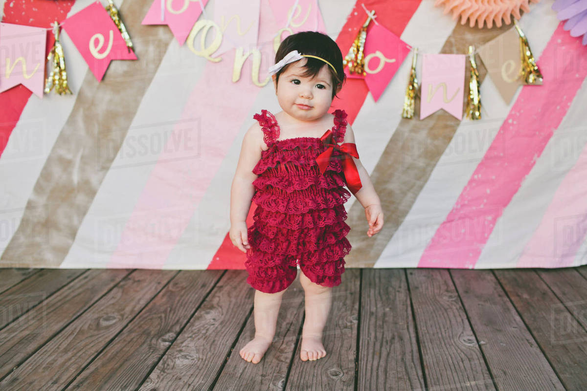 cute baby girl standing on floorboard at birthday party - stock