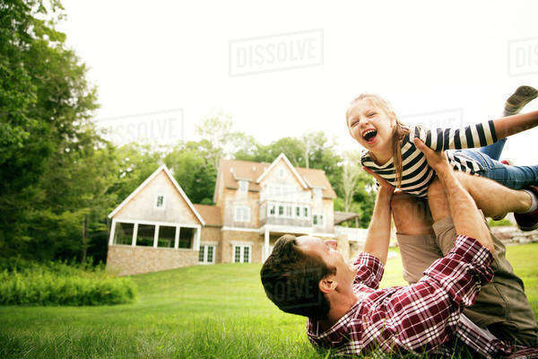 Girl (6-7) laughing with her father in backyard Royalty-free stock photo