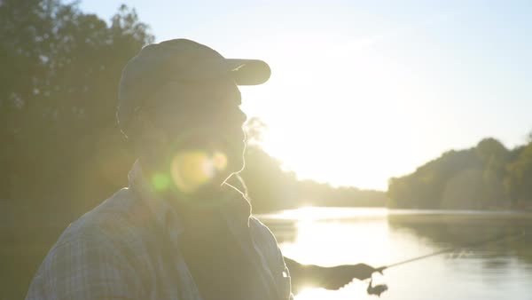 Close-up handheld shot of smiling man fishing with son on lake during sunny day Royalty-free stock video