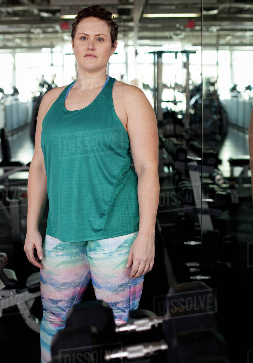 Portrait Of Woman Standing By Dumbbells In Gym Stock Photo