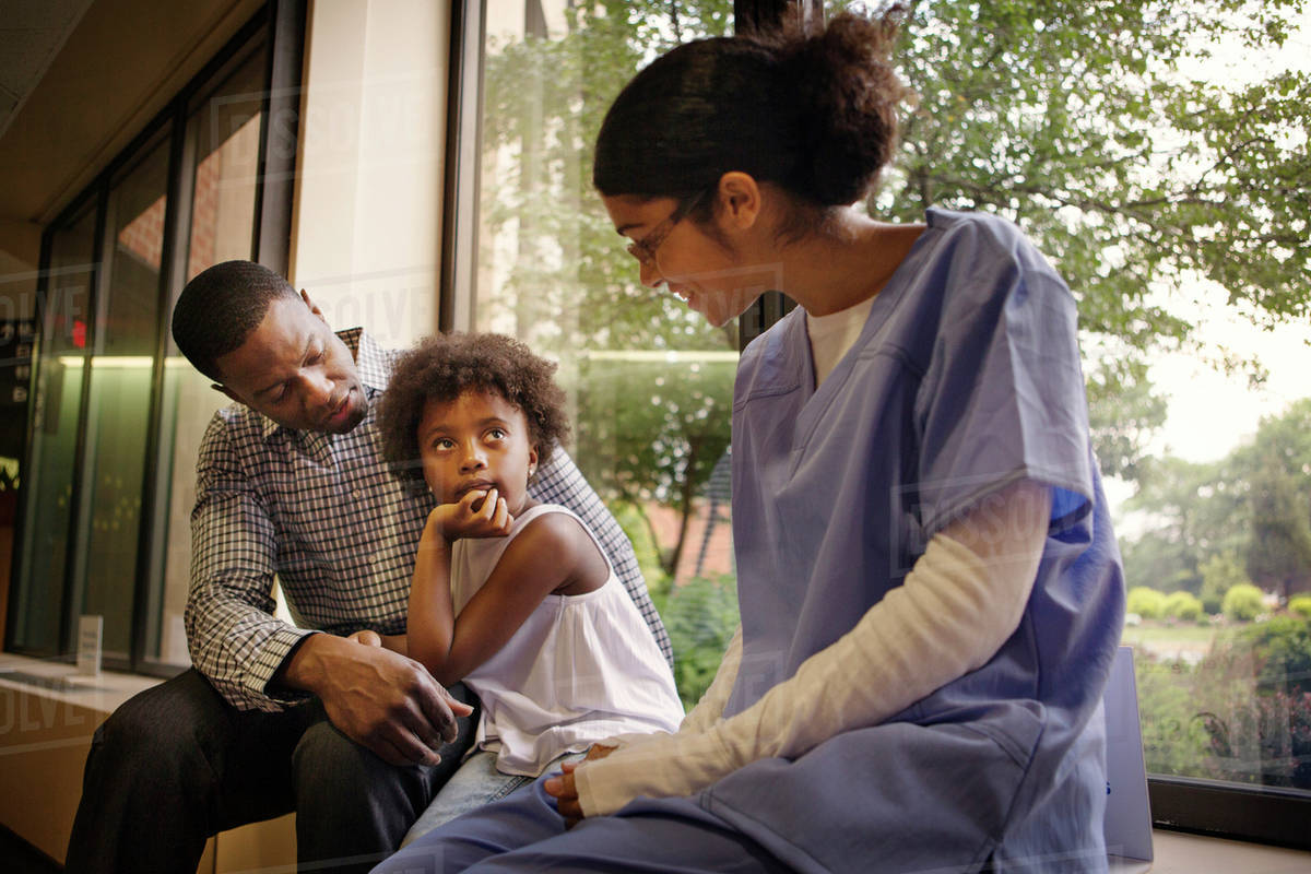 Nurse talking to girl (4-5) and her father in hospital Royalty-free stock photo