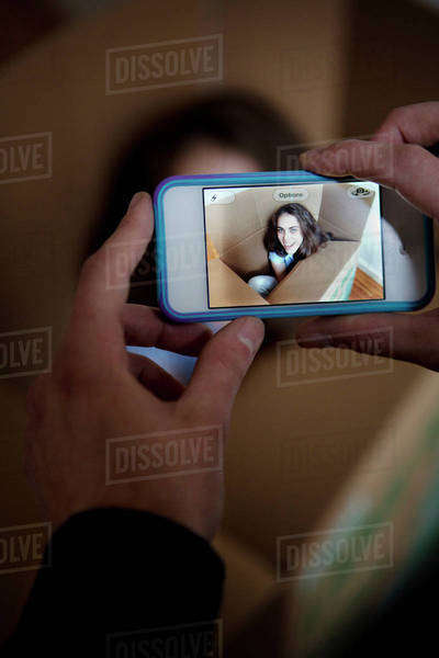 Man photographing woman sitting in cardboard box with smartphone Royalty-free stock photo