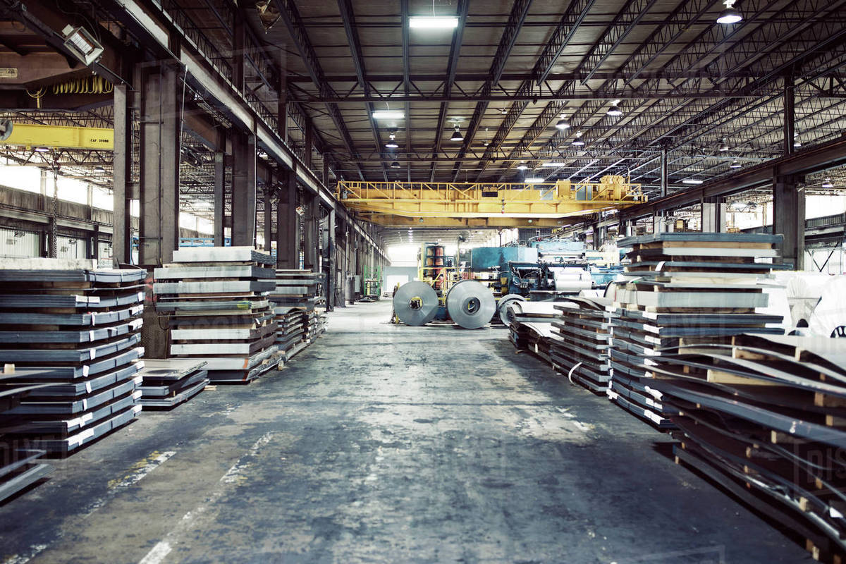 metal sheets and machineries in warehouse stock photo dissolve