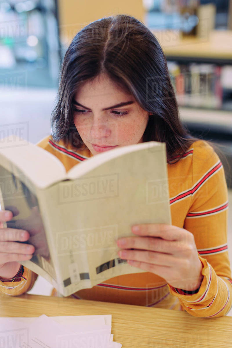 woman reading book while sitting at table in library stock photo