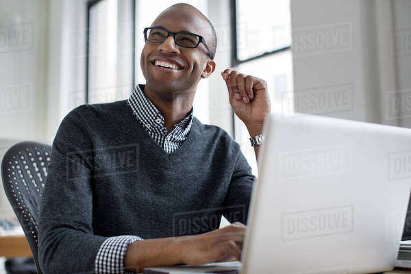 Happy businessman looking away while working on laptop in creative office Royalty-free stock photo