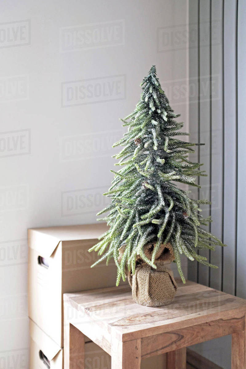 Christmas Tree On Wooden Table By Cardboard Boxes At Home Stock