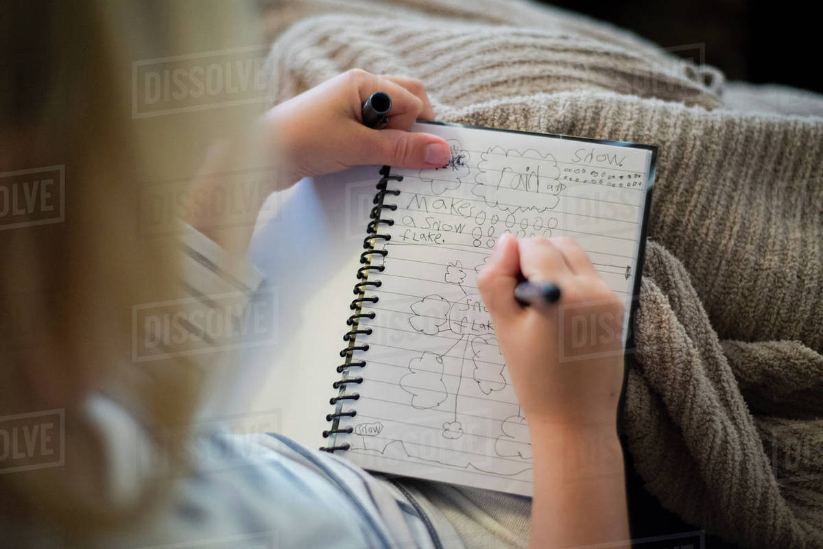 High angle view of girl writing in diary while sitting at