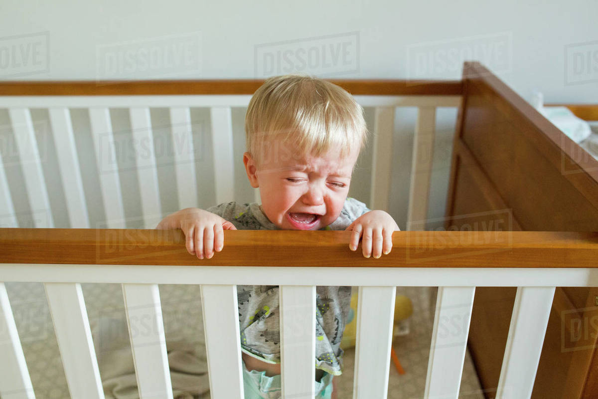 Baby boy crying while standing in crib at home - Stock ...