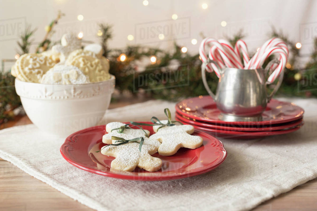 Close Up Of Gingerbread Cookies With Christmas Decorations On Table Against Illuminated Lights Stock Photo