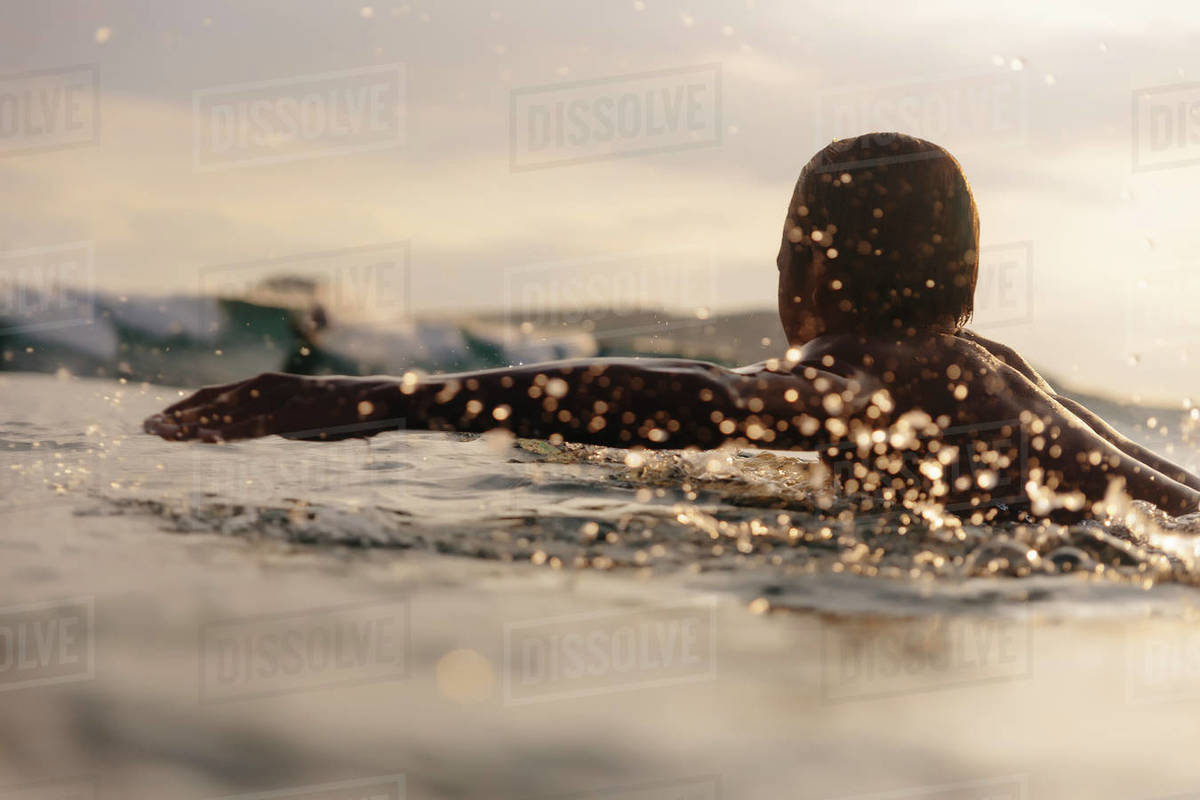 Man surfing on sea against cloudy sky during sunset Royalty-free stock photo