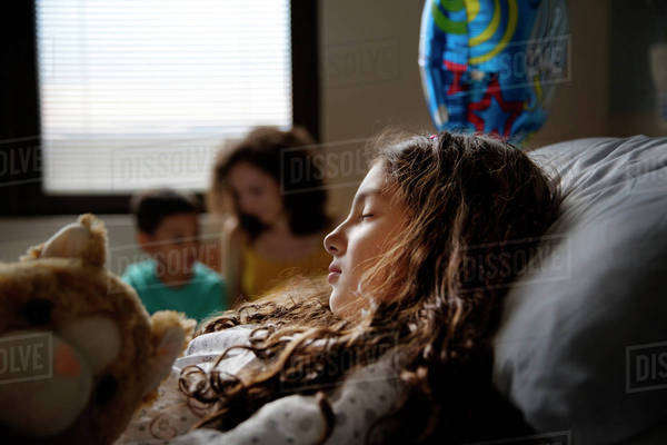 Girl (8-9) sleeping in hospital ward and mother on background Royalty-free stock photo