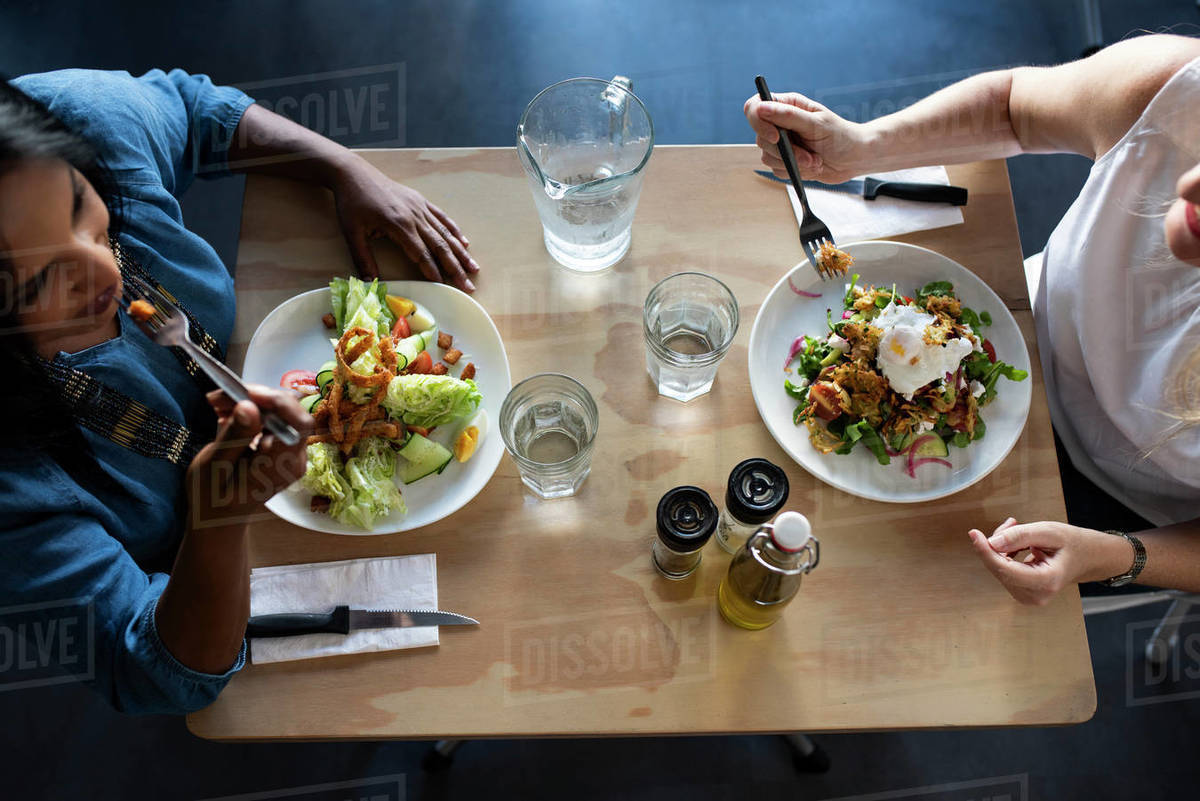 High Angle View Of Friends Talking While Eating Food On Table In Cafeteria Stock Photo