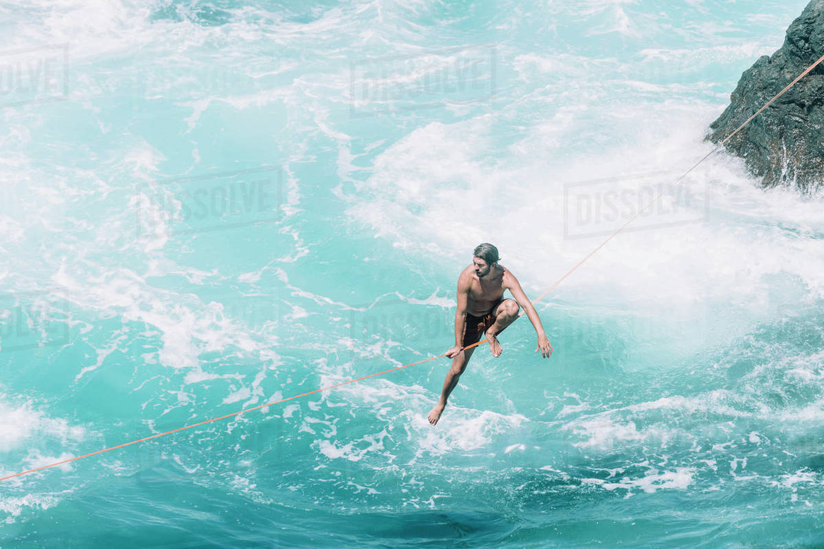 High angle view of carefree young man slacklining on rope over sea during sunny day Royalty-free stock photo