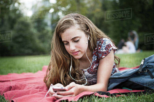 Teenager listening music while lying on picnic blanket at park Royalty-free stock photo