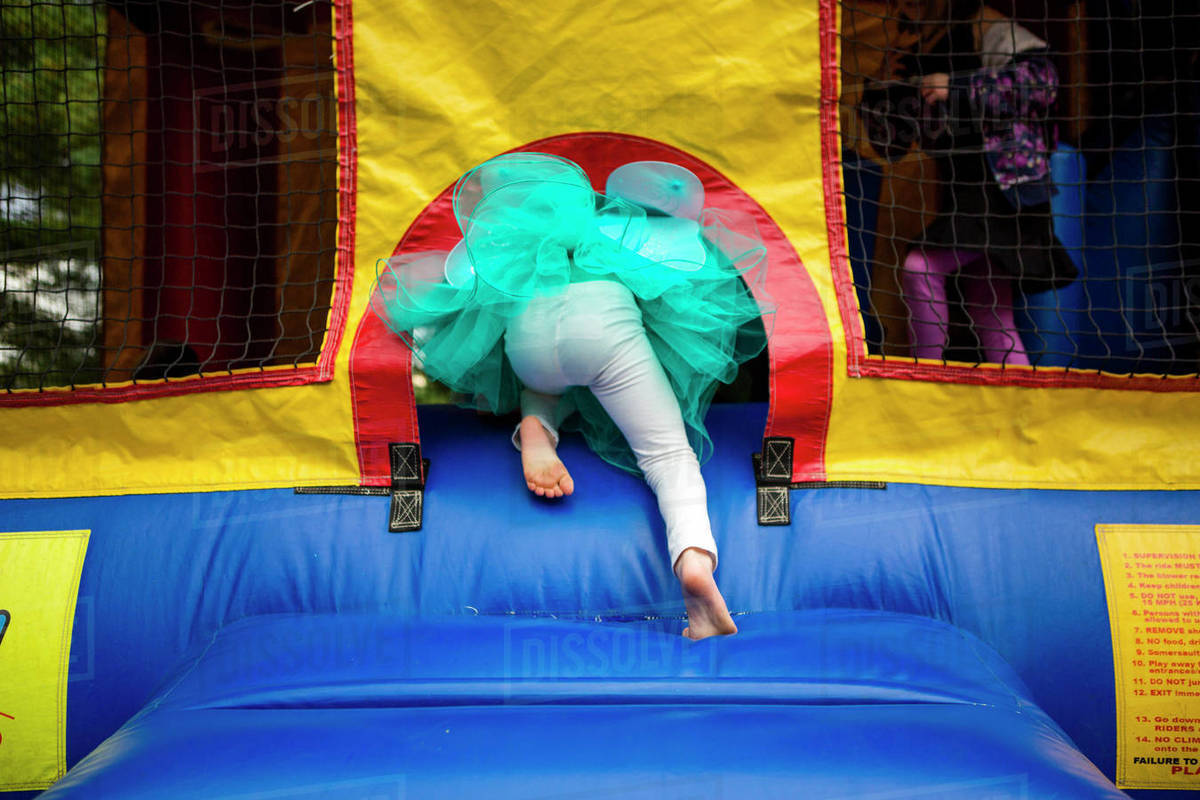 The bottom half of a child in a tutu climbing into a bouncehouse Royalty-free stock photo