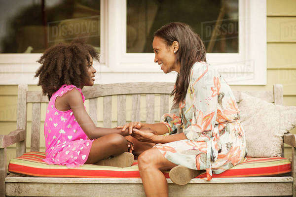 Mother with daughter (8-9) sitting on bench in front of house Royalty-free stock photo