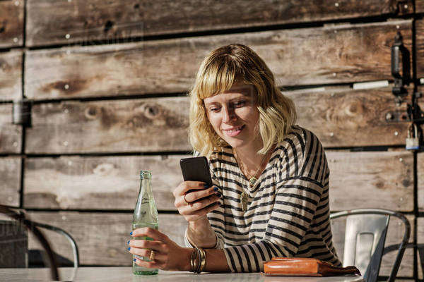 Woman drinking water and using smart phone Royalty-free stock photo