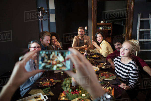 Cropped image of woman photographing happy friends while enjoying meal Royalty-free stock photo