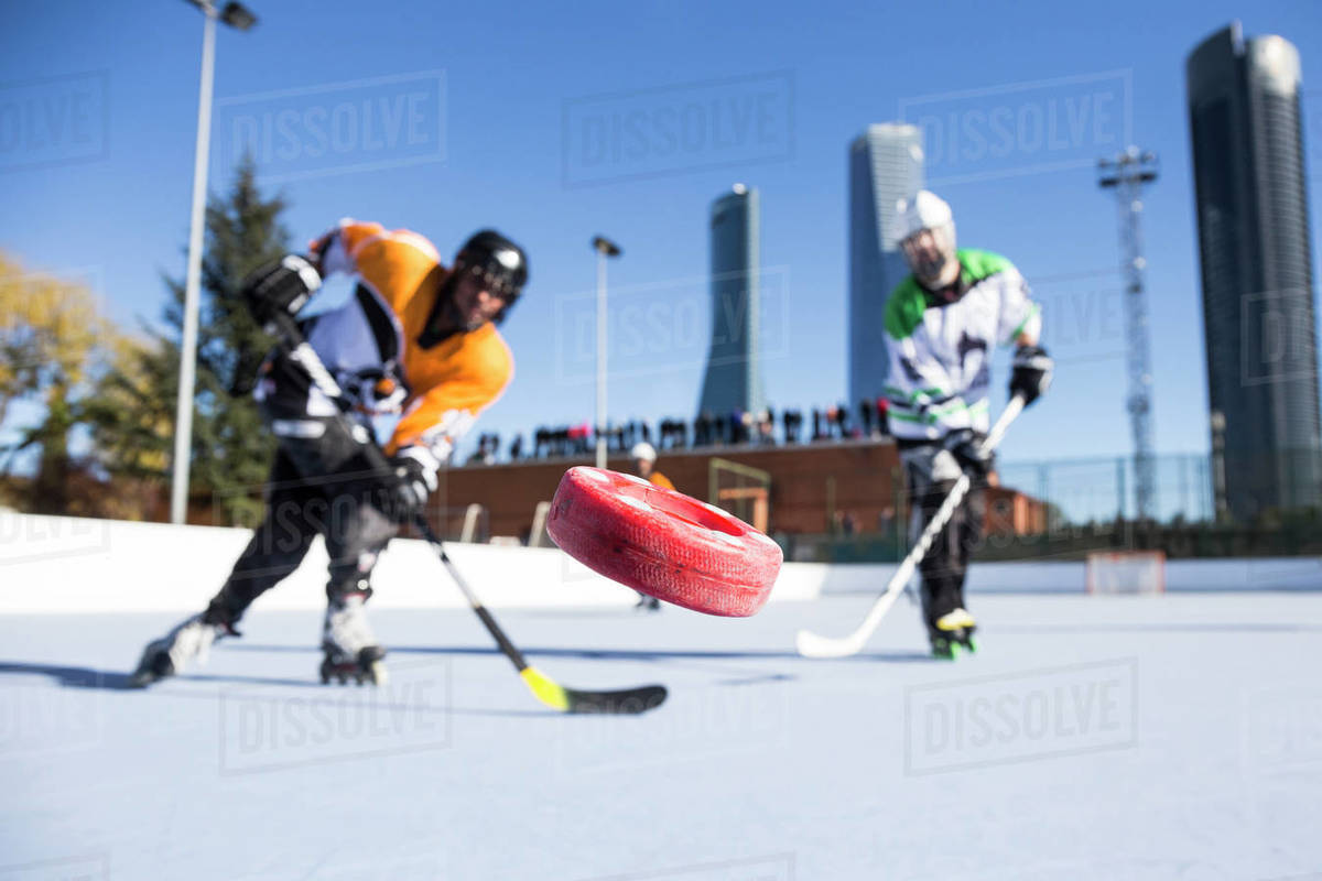 In-line hockey players hit the puck at camera in sunny day. Royalty-free stock photo