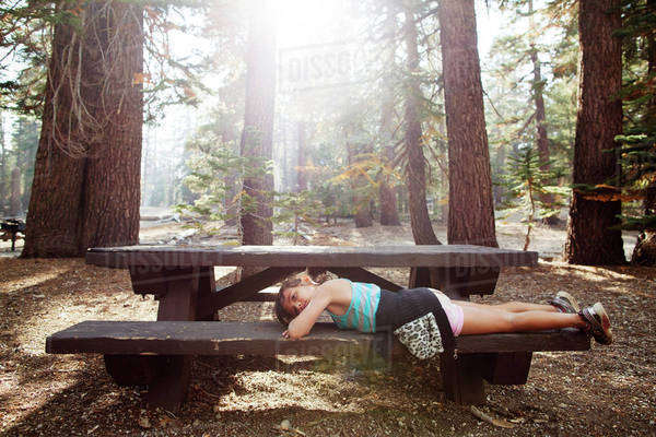 Side view of girl lying on bench amidst trees in forest Royalty-free stock photo
