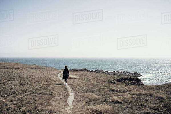 Woman walking on cliff by sea against clear sky Royalty-free stock photo