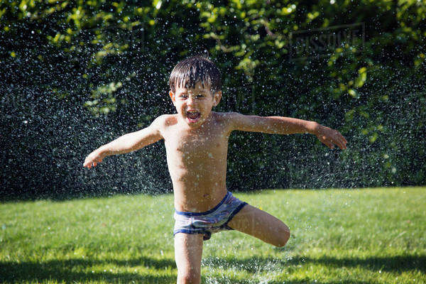 Boy jumping over water sprinkler on grassy field Royalty-free stock photo