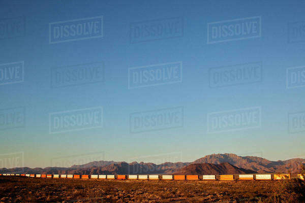 Freight Train at field against clear blue sky Royalty-free stock photo
