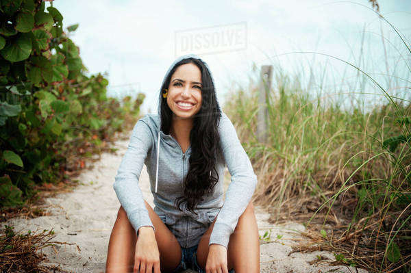 Young woman sitting on beach path Royalty-free stock photo