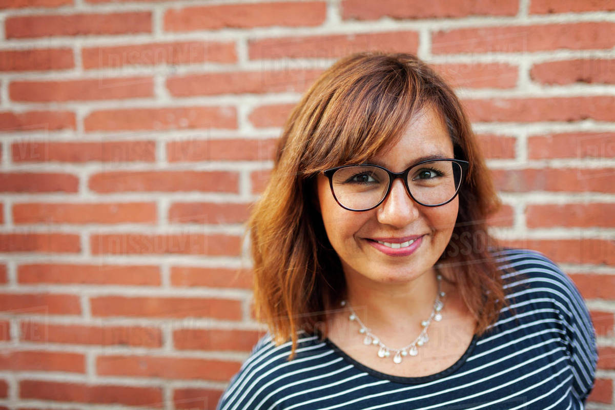 Close-up portrait of smiling woman wearing eyeglasses against brick wall Royalty-free stock photo