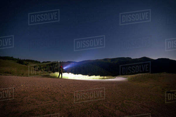 Distant view of hiker with illuminated flashlight on hill against clear sky Royalty-free stock photo