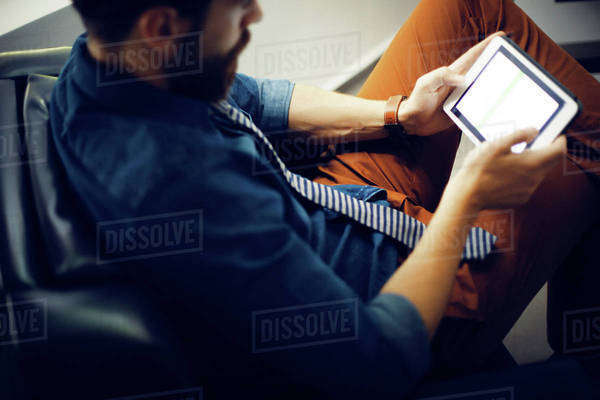 Man sitting in armchair and using digital tablet Royalty-free stock photo