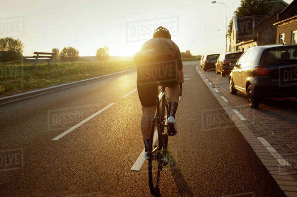 Rear view of man cycling on road by parked cars against sky Royalty-free stock photo