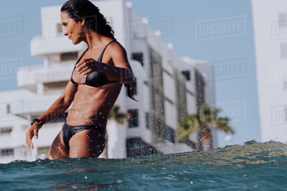 Female surfer in bikini on wave seen from behind Royalty-free stock photo