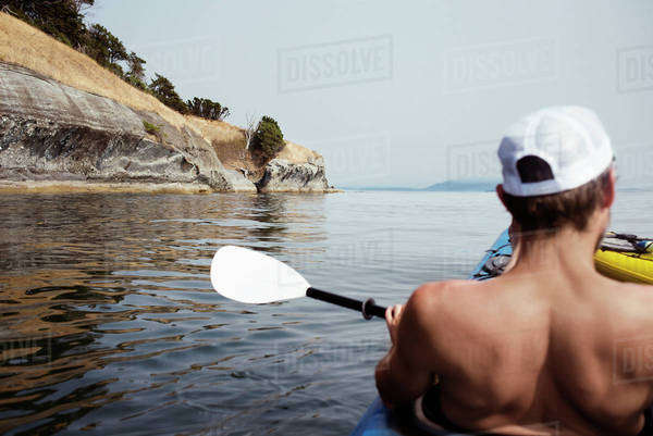 Shirtless man relaxing on kayak at Strait of Georgia Royalty-free stock photo