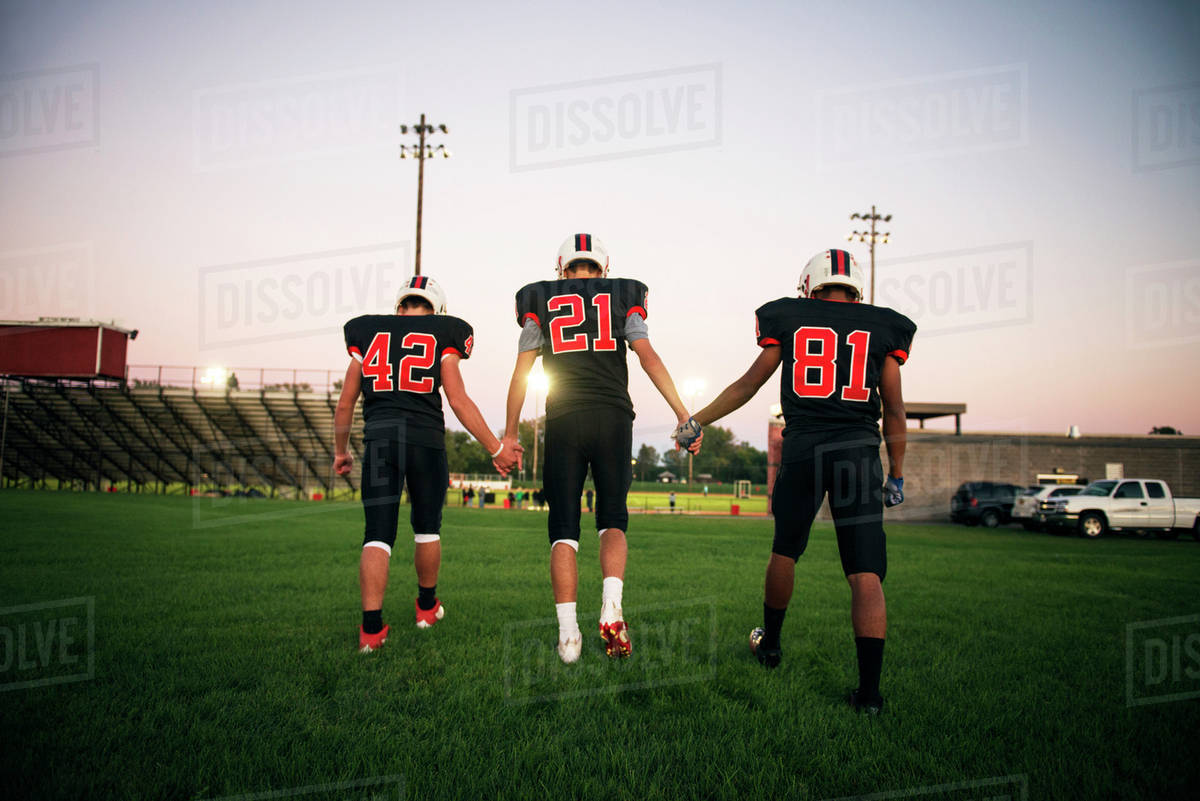 Football players (16-17) holding hands on playing field Royalty-free stock photo