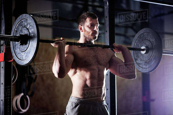 Confident man lifting barbells in gym Royalty-free stock photo