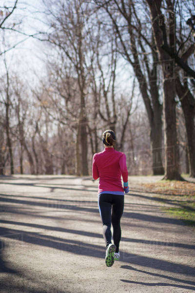Rear view of woman running on road against bare trees Royalty-free stock photo