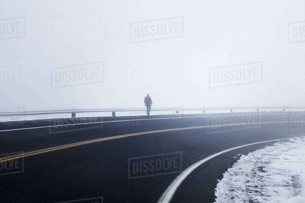 Man walking on highway during foggy weather Royalty-free stock photo