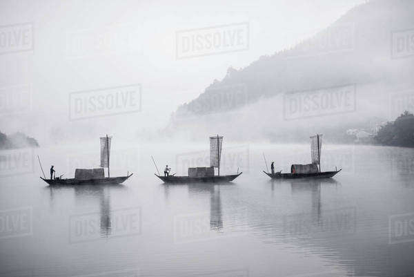 Men rowing traditional boats in lake during foggy weather Royalty-free stock photo