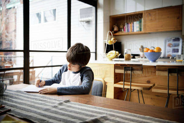 Boy writing in book on table at home Royalty-free stock photo